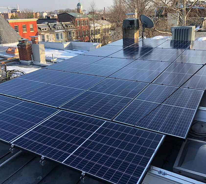 A solar electric system installed on parapets of a flat roof in Washington DC